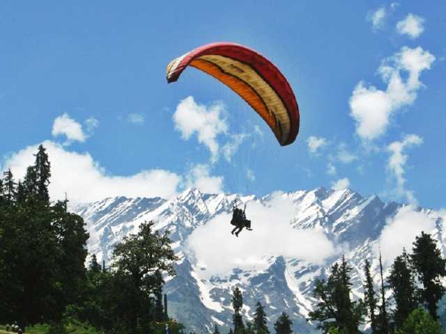 man-flying-with-triangular-parachute-in-sky-with-snowy-mountains-in-backdrop-manali-mounty.co